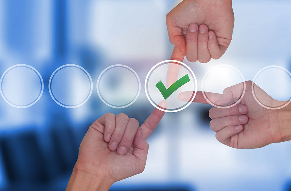 Team work hands touching check mark on virtual screen. Business technology concept. Isolated on office. Stock Image